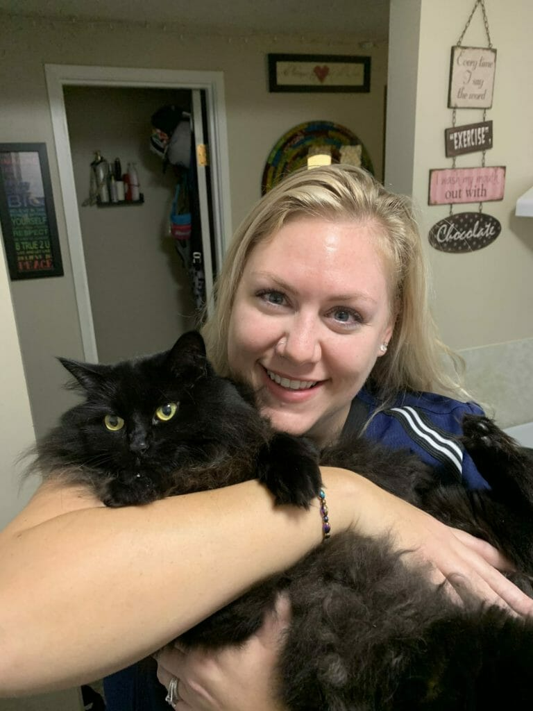 Receptionist holding a black cat