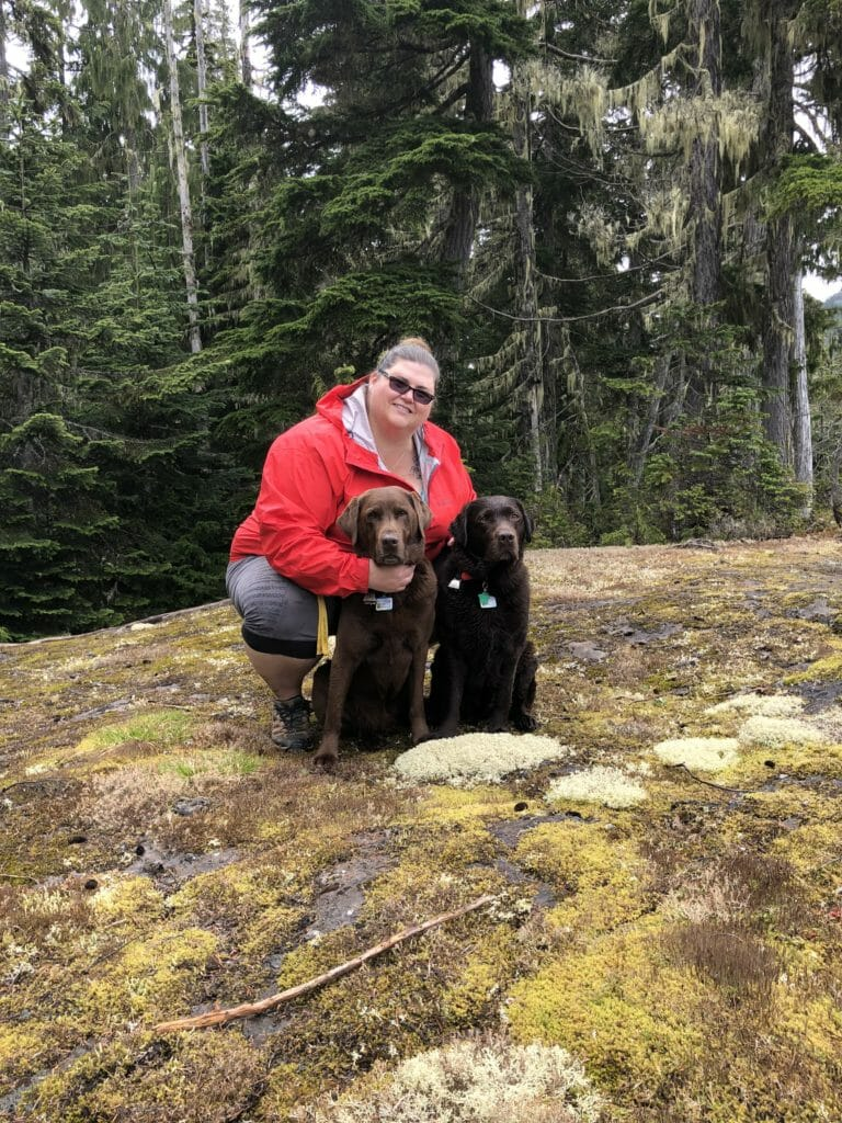 Hospital manager in forest next to two brown dogs